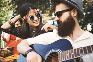 Young boho couple playing acoustic guitar at festival - ISF05825