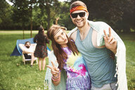 Portrait of young boho couple making peace signs at festival - ISF05831