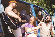 Five young adult friends playing acoustic guitar and clapping by recreational van - ISF05846