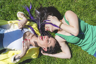 Women lying on grass laughing - ISF05894