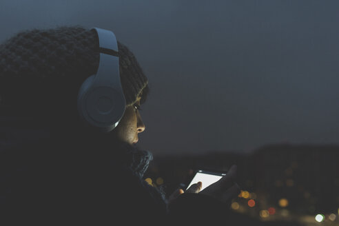 Woman wearing headphones looking at smartphone in city at night - ISF05948