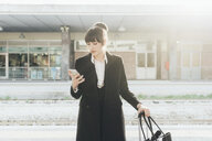 Businesswoman using mobile phone in train station, Milan, Italy - ISF05957