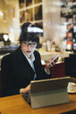 Businesswoman using mobile phone and digital tablet in cafe - ISF05978