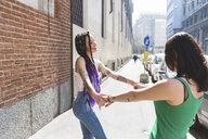 Women on city break dancing in street, Milan, Italy - ISF06002