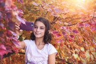 Young girl in rural setting, taking selfie with smartphone - ISF06017