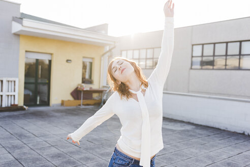 Beautiful young woman dancing on sunlit roof terrace with eyes closed - ISF06056