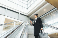 Businesswoman using mobile phone on escalator, Milan, Italy - ISF06101