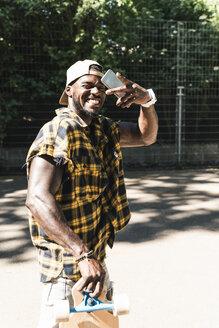 Cool young man in skate park, taking smartphone selfie - UUF13837