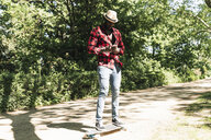 Cool young man skateboarding in park, using smartphone - UUF13846