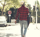 Cool young man with skateboard walking in the city, - UUF13849