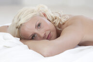 Portrait of beautiful naked young woman lying on bed - CUF13193