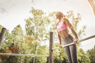Mature women in park doing push ups on metal bar looking away smiling - CUF13223
