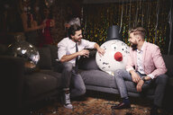 Two men sitting on sofa at party, giant snowman head in-between them, laughing - ISF06133