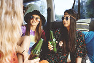 Three young boho women relaxing in recreational van - ISF06284