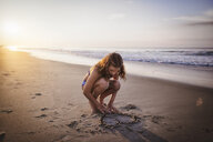 Girl drawing heart in sand on beach - ISF06302