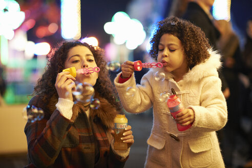Mother and daughter blowing bubbles, at funfair - CUF13406
