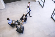 High angle view of businesswoman and men meeting in office atrium - CUF13553