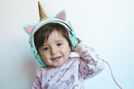 Portrait of smiling baby girl with unicorn headphones listening music - GEMF02009