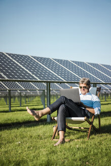 Mature man sitting in sun lounger, using laptop, solar plant - MOEF01122