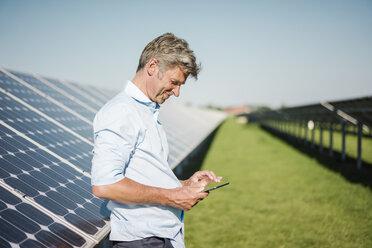 Businessman using tablet at solar park - MOEF01125