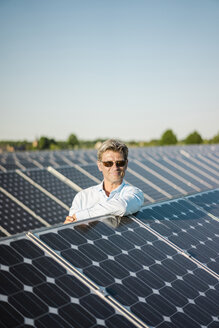 Smiling mature man with sunglasses leaning on solar panel - MOEF01128