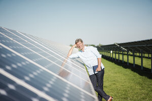 Mature man with tablet leaning on panel in solar plant - MOEF01131