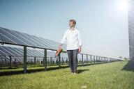 Mature man walking barefoot on meadow between solar panels - MOEF01137