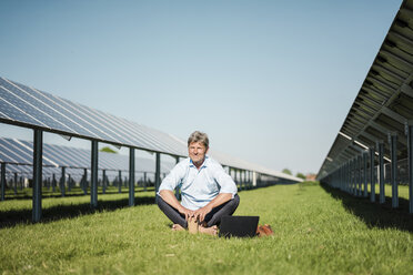 Mature man sitting barefoot on meadow, laptop and coffee to go cup, solar plant - MOEF01140