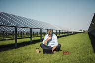 Mature man sitting barefoot on meadow, laptop and coffee to go cup, solar plant - MOEF01143