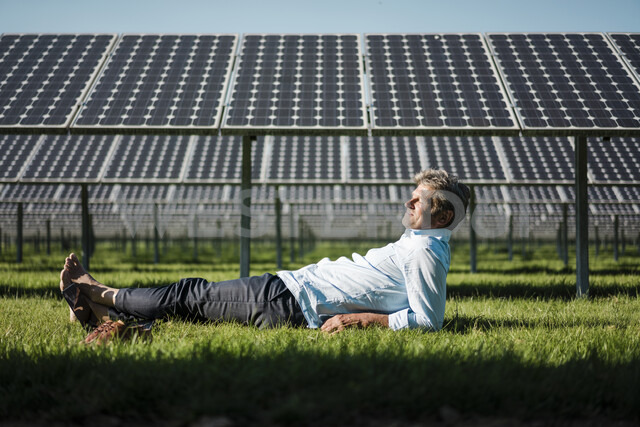 Mature man lying barefoot on meadow, solar plant - MOEF01146