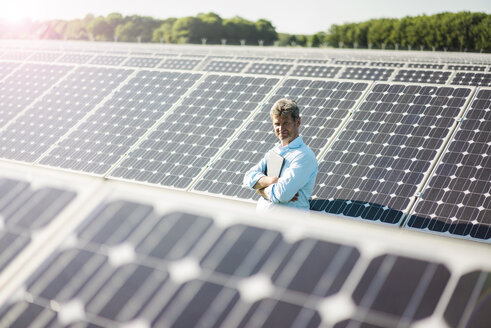 Mature man with laptop standing in solar plant - MOEF01149