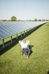 Mature man sitting in sun lounger, solar plant - MOEF01152
