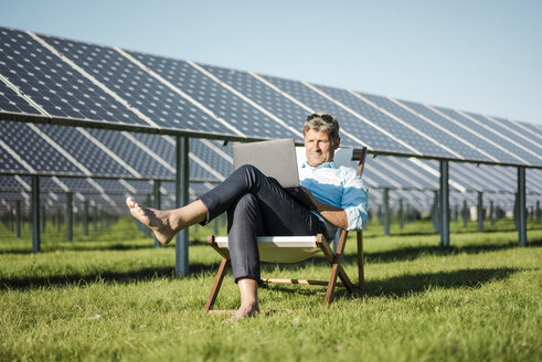 Mature man sitting in beach lounger, using laptop, solar plant - MOEF01155