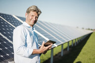 Businessman using tablet at solar park - MOEF01158