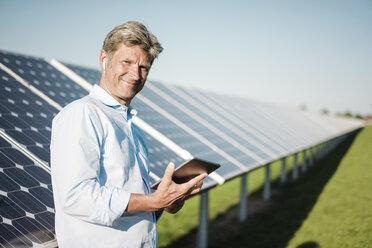 Businessman using tablet at solar park - MOEF01158