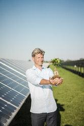Mature man looking at privet, solar plant - MOEF01164