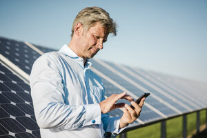 Businessman using smartphone at solar park - MOEF01173
