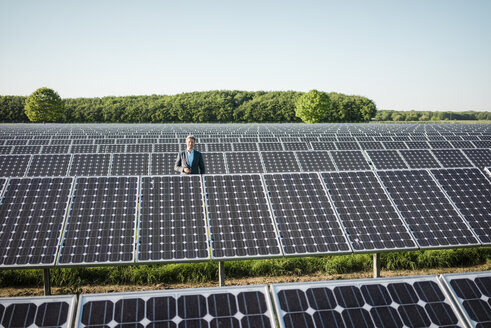 Mature man standing on panel in solar plant - MOEF01176