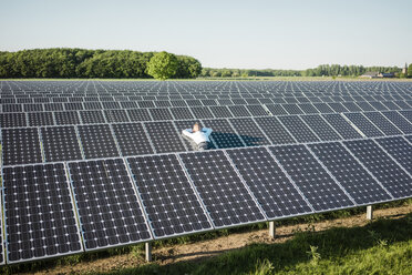 Mature man resting on panel in solar plant - MOEF01179