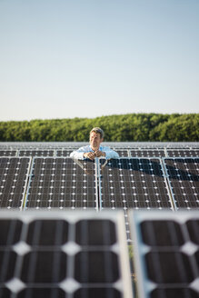 Mature man standing in solar plant - MOEF01182