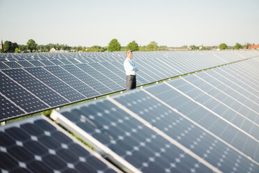 Mature man standing in solar plant - MOEF01185