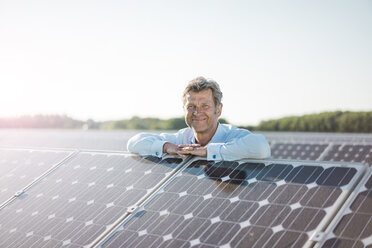 Smiling mature man standing in solar plant - MOEF01188