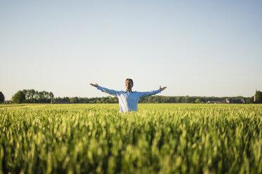 Businessman standing in grain field, raised arms - MOEF01191