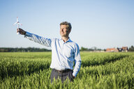Businessman standing in grain field, holding miniature wind wheel - MOEF01194