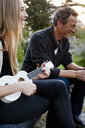 Couple sitting together, woman playing ukulele - CUF13720