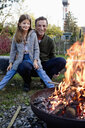 Girl sitting on father's lap in garden watching fire pit - CUF13726