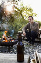 Mature man sitting by fire pit with beer, relaxing - CUF13729