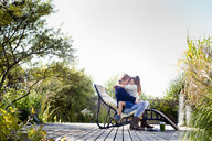 Mother and daughter hugging on lounge chair on decking - CUF13744