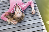 Young woman lying on wooden decking smiling to camera - CUF13768