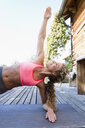 Young woman in side plank pose - CUF13774